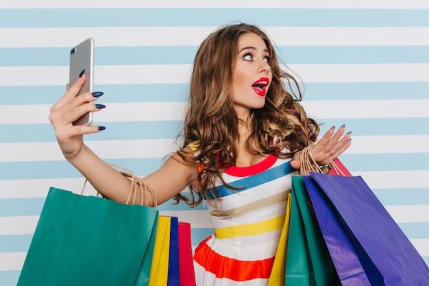 Emotionele vrouwelijke shopaholic selfie maken. betoverend blank meisje dat na het winkelen voor de gek houdt.