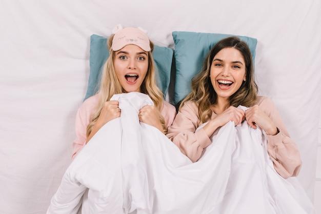 Emotionele vrouwen die onder een deken liggen