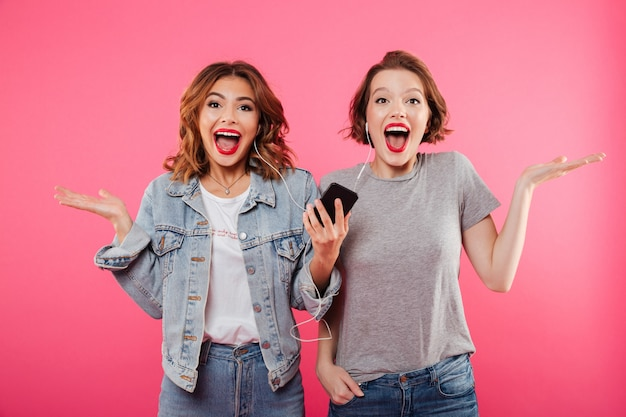 Emotionele vrouwenvrienden die mobiele telefoon het luisteren muziek gebruiken.