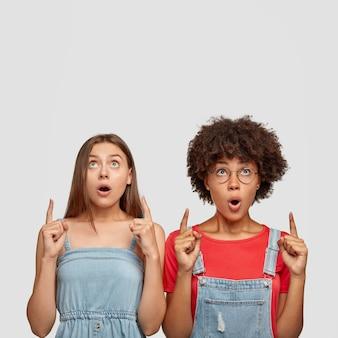 Emotionele vrouwtjes van gemengd ras houden hun mond open, wijs naar lege kopie ruimte