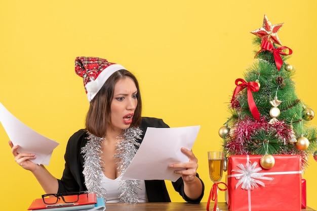 Emotionele zakelijke dame in pak met kerstman hoed en nieuwjaarsversieringen documenten controleren en zitten aan een tafel met een kerstboom erop in het kantoor