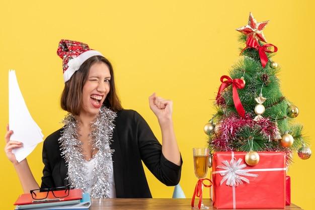 Emotionele zakelijke dame in pak met kerstman hoed en nieuwjaarsversieringen met documenten en zittend aan een tafel met een kerstboom erop in het kantoor