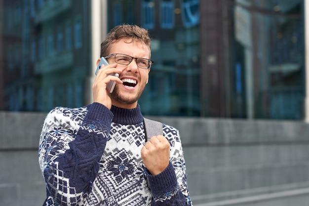 Emotionele zakenman freelancer praten aan de telefoon. succesvol gesprek met een partner of klant, goed koopje