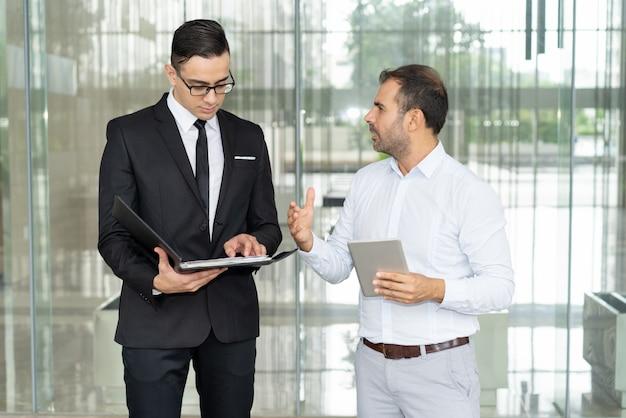 Emotionele zakenman met tablet die zijn punt bewijst