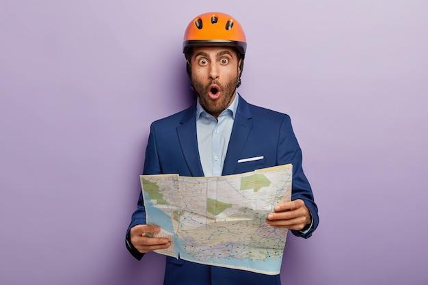 Emotionele zakenman poseren in stijlvol pak en rode helm op kantoor