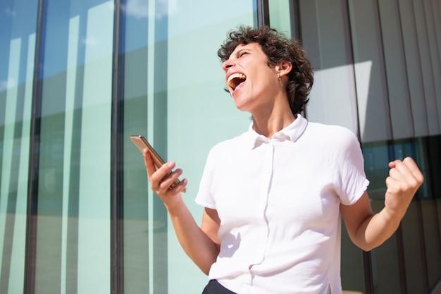 Emotionele zakenvrouw met smartphone