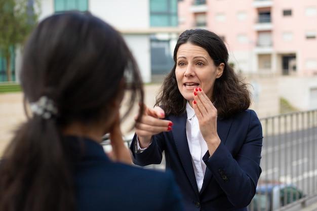 Emotionele zakenvrouw praten met collega