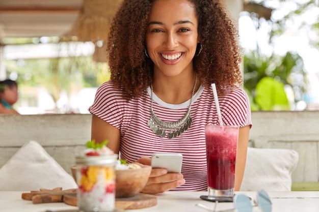 Emotionele zwarte jonge vrouw met fris haar, brede glimlach, moderne cellulaire bezit, maakt gebruik van gratis wifi in cafetaria voor netwerken, drinkt vers fruit smoothie, draagt casual t-shirt, heeft vrije tijd