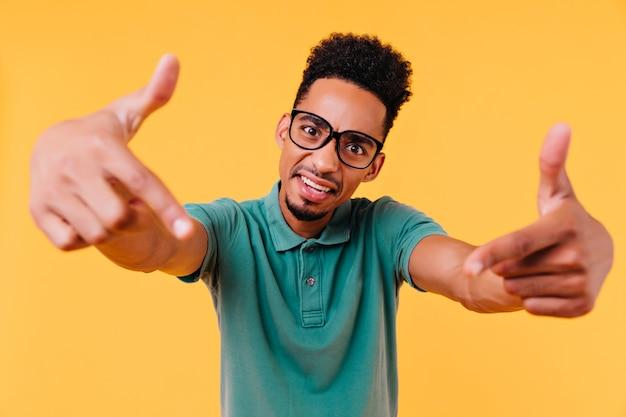 Emotionele zwartogige man poseren. geïnspireerde afrikaanse man met kort haar die grappige gezichten maakt.