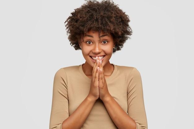 Emotive blij donkere huid meisje heeft brede glimlach, houdt de handen in biddend gebaar