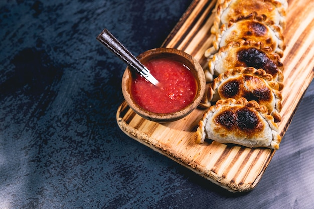 Empanadas op een houten bord en hete saus