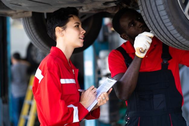Empowerment van kaukasische waman-monteur die rood uniform draagt en werkt onder een voertuig in een auto-servicestation