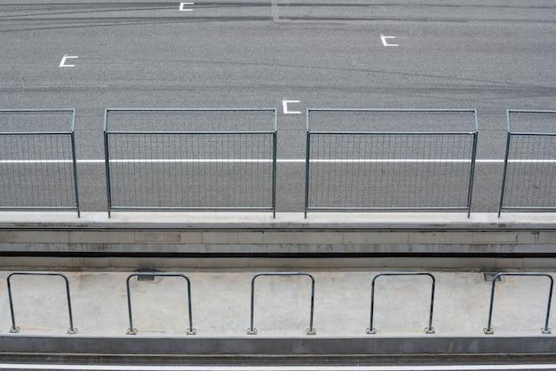 Empty asfalt wegcircuit en veiligheidshek met startpositie view from tribune.