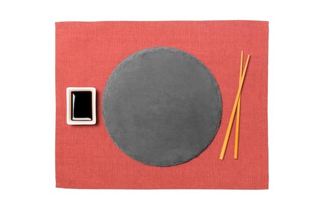 Emptyround zwarte lei plaat met stokjes voor sushi en sojasaus op rode servet oppervlak