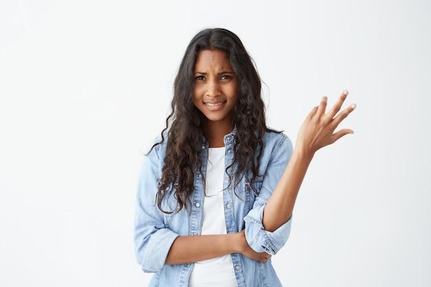 En dan. clueless verbaasde afro-amerikaanse vrouw gebaart met handen in onwetendheid en verwarring, haalt haar schouders op. negatieve gevoelens en emoties.