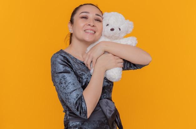 En de positieve aziatische teddybeer die van de vrouwenholding vrolijk glimlacht