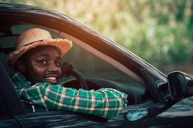 En landbouwer die terwijl het zitten in een auto met open voorruit drijven kijken