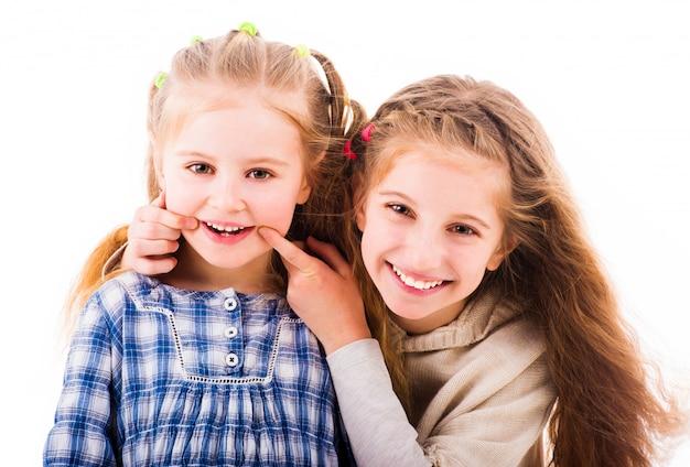 En meisjes die samen glimlachen ontspannen op witte achtergrond