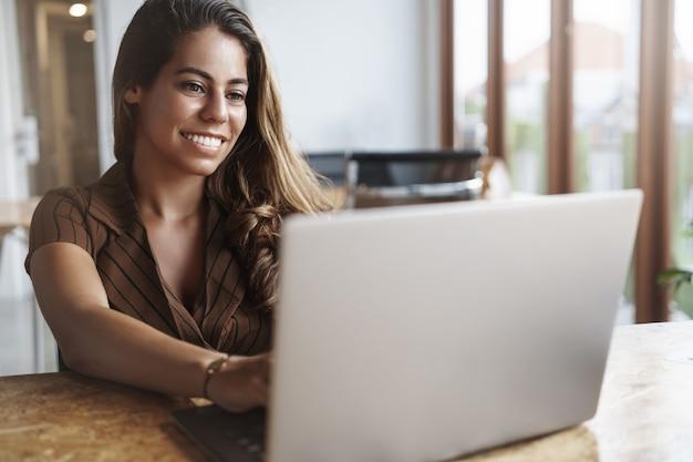 En succesvolle spaanse vrouw die lacht met behulp van laptop in café