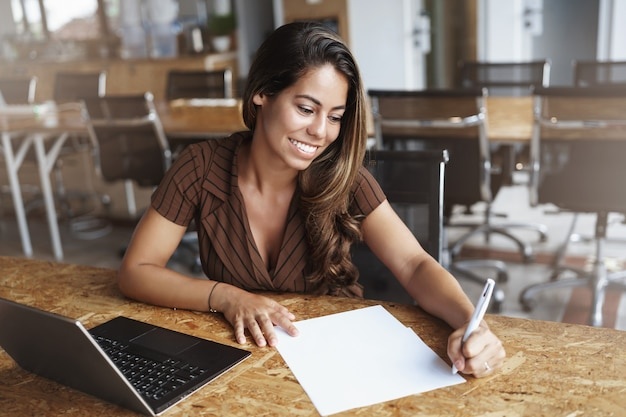 En succesvolle spaanse vrouw die lacht werken in café Gratis Foto