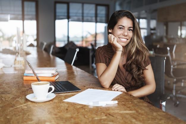 En succesvolle spaanse vrouw die lacht werken in café