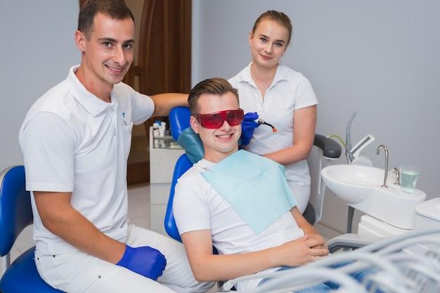 En tandarts en patiënt die stellen glimlachen