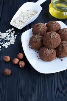 Energie ballen met hazelnoot, cacao, haver granen en honing op de witte plaat op de zwarte houten tafel.