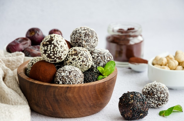 Energie ballen. truffels van dadels, walnoten, hazelnoten en cacao in een houten kom op een lichte achtergrond. gezond dessert, suikervrij, glutenvrij. horizontale oriëntatie.