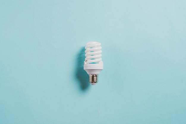 Energie - besparings compacte neonlichtbol op blauwe achtergrond