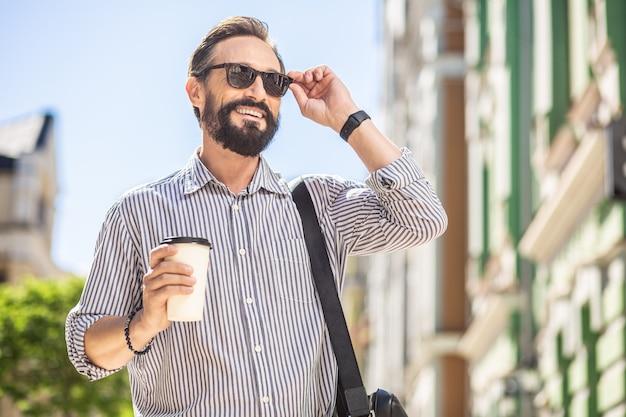 Energie booster. vrolijke stijlvolle man koffie drinken tijdens het wandelen in de straat