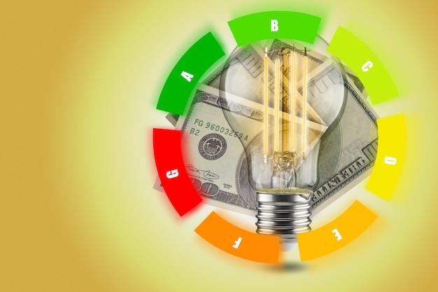 Energie-efficiëntieconcept van led-lampen. daling van het elektriciteitsverbruik. led-lamp met dollars op een gele achtergrond. ronde tafel.