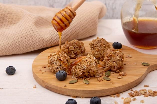 Energie granola bites met honing op een houten bord.