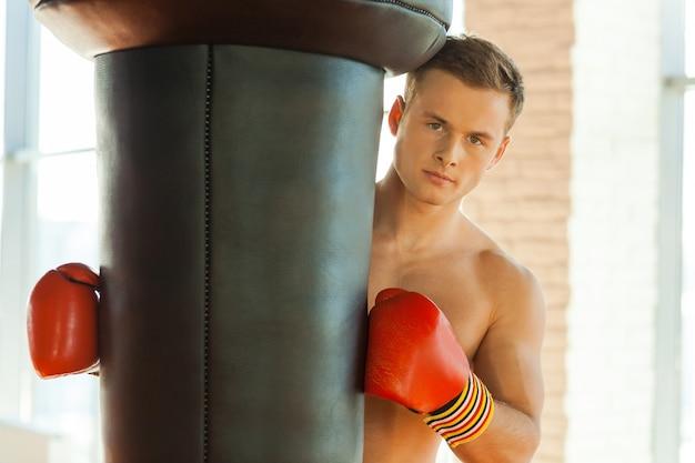 Energie in mij. zelfverzekerde jonge bokser in sporthandschoenen die naar de bokszak leunt en naar de camera kijkt