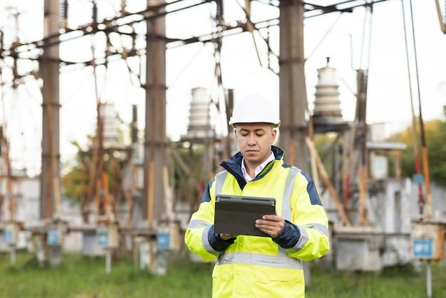 Energie-ingenieur man in speciale kleding inspecteert een hoogspanningslijn met behulp van gegevens van elektrische sensoren