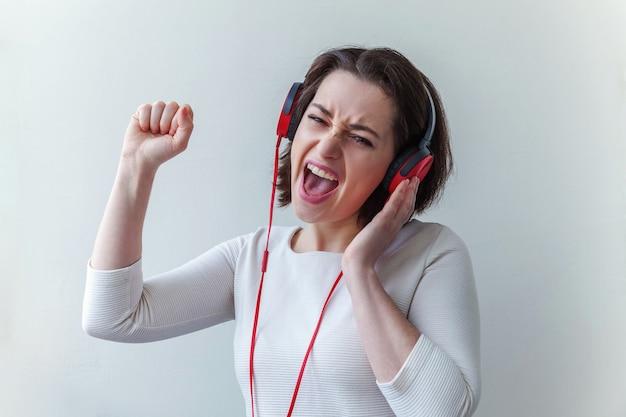 Energie jonge brunette dame vrouw luisteren muziek in hoofdtelefoons en zingen geïsoleerd op wit