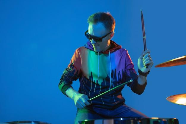 Energie. jonge geïnspireerde en expressieve muzikant, drummer die optreedt op een gekleurde muur in neonlicht. concept van muziek, hobby, festival, kunst. vrolijke kunstenaar, kleurrijk, helder portret.