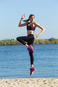 Energie. jonge vrouwelijke atleet, vrouw training, buiten oefenen in de herfstzon