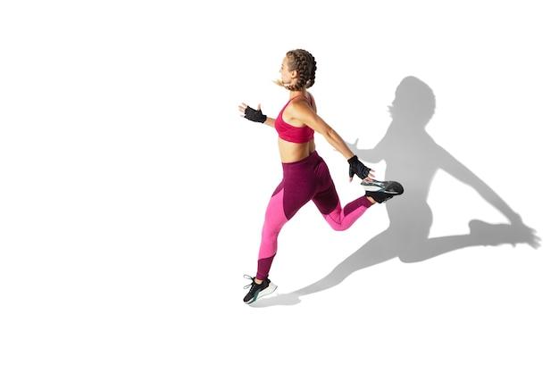 Energie. mooie jonge vrouwelijke atleet oefenen op witte muur, portret met schaduwen. sportief fit model in beweging en actie. lichaamsbouw, gezonde levensstijl, stijlconcept.