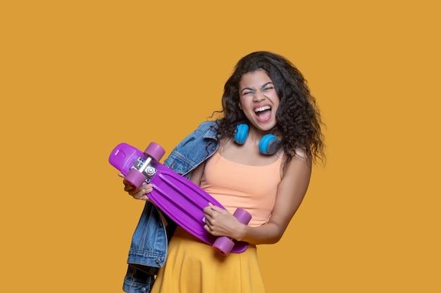 Energie. vrij donkerharig jong meisje met een skateboard