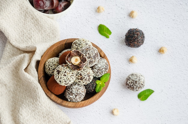 Energieballen. truffels van dadels, walnoten, hazelnoten en cacao in een houten kom op een lichte achtergrond.