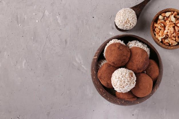 Energieballen van noten en havermout met kokosvlokken en cacao in kokoskom op grijs oppervlak, horizontaal formaat, bovenaanzicht, kopie ruimte