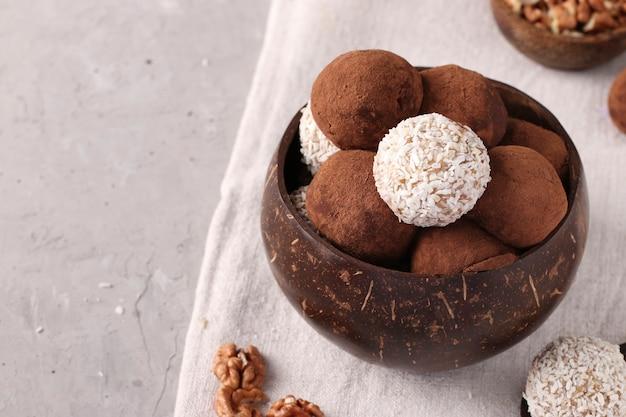 Energieballen van noten en havermout met kokosvlokken en cacao in kokoskom op grijze achtergrond, horizontaal formaat, kopieer ruimte