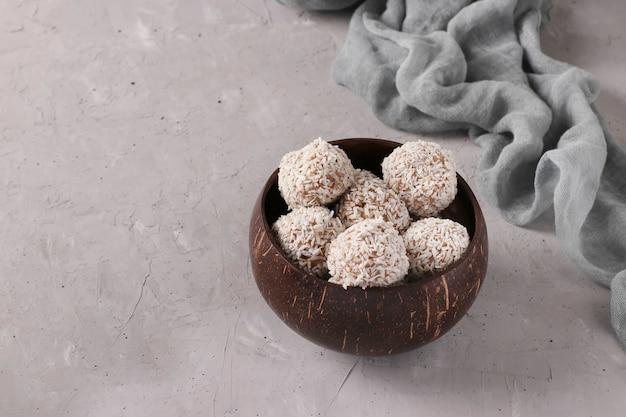 Energieballen van noten en havermout met kokosvlokken in kokosnootkom op grijze achtergrond, horizontaal formaat, exemplaarruimte