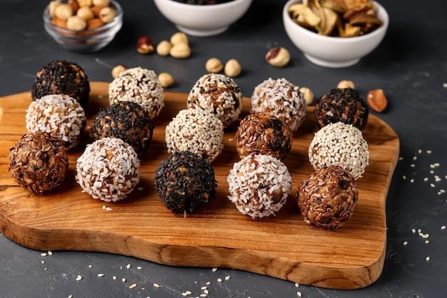 Energieballen van noten, havermout en gedroogd fruit op houten bord op donkere achtergrond