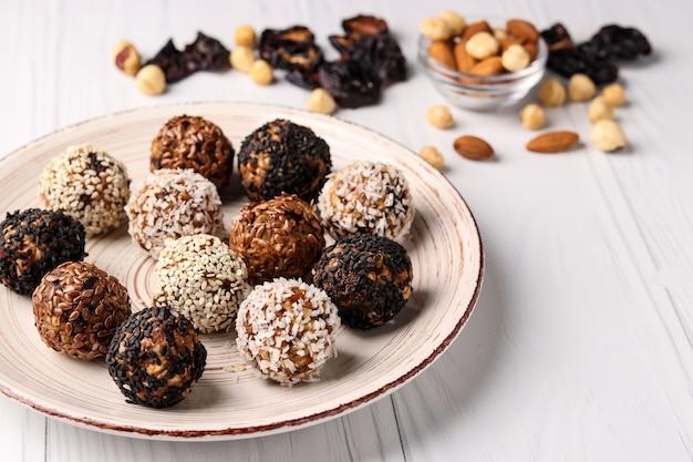 Energieballen van noten, havermout en gedroogde vruchten op een plaat op een wit oppervlak, horizontale oriëntatie, close-up