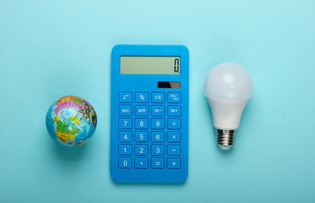 Energiebesparend. calculator met geleide gloeilamp en bol op blauwe pastelkleurachtergrond. red de planeet. eco concept. bovenaanzicht