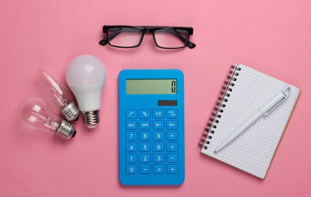 Energiebesparend. rekenmachine met gloeilampen, bril, notitieboekje op roze blauw pastel