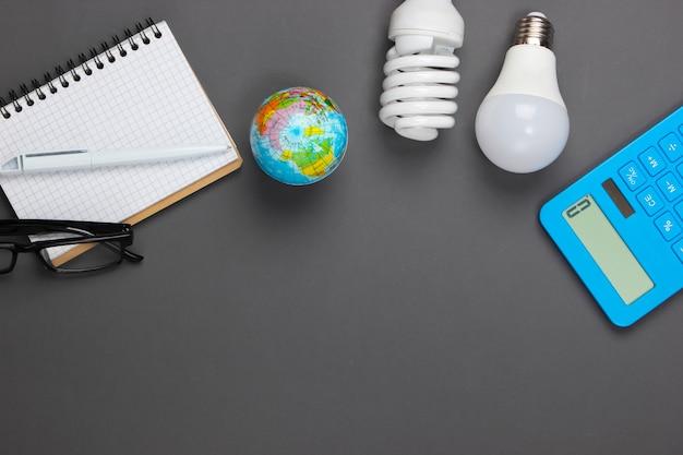 Energiebesparende analyses. rekenmachine met gloeilampen, notebook, globe op grijs. kopieer ruimte