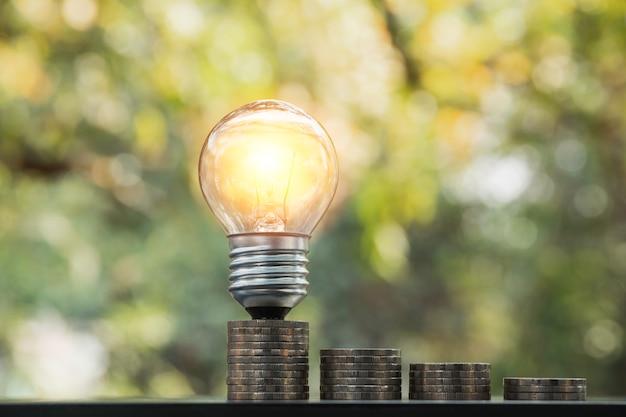 Energiebesparende gloeilamp met stapels munten voor opslaan, financiële en boekhoudkundige