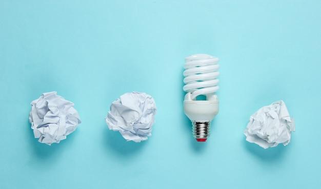 Energiebesparende lamp en verfrommeld papier ballen op blauwe tafel. minimalistisch bedrijfsconcept, idee. bovenaanzicht